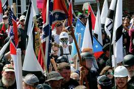 """FILE- In this Saturday, Aug. 12, 2017, photo white nationalist demonstrators walk into the entrance of Lee Park surrounded by counter demonstrators in Charlottesville, Va. The Detroit Lions said Tuesday, Aug. 15, that they """"detest and disavow"""" any use of their logo associated with the event Saturday in Charlottesville. A photo taken at the demonstration showed someone with a logo similar to the one the Lions use, although it was blue and red and had stars on it. (AP Photo/Steve Helber, File) ORG XMIT: NYJK313"""