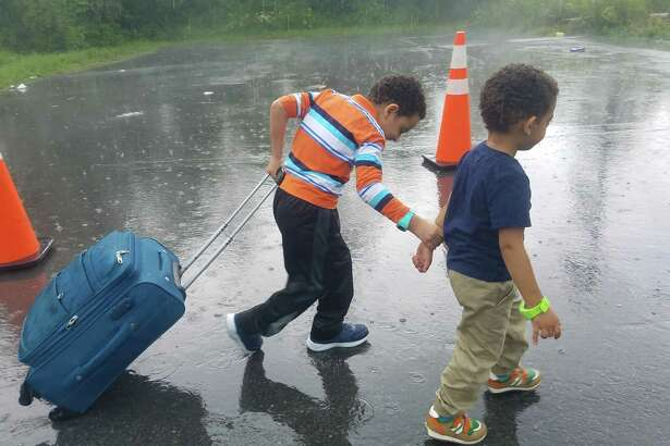 In pouring rain, two young boys make their way toward the illegal border crossing at the end of Roxham Road in Champlain, N.Y. The rural roadway is attracting migrants from around the country who plan to leave the United States to seek political asylum in Canada. (Chris Churchill / Times Union)