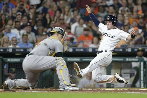 HOUSTON, TX - AUGUST 19: Alex Bregman #2 of the Houston Astros slides home against Bruce Maxwell #13 of the Oakland Athletics in the fifth inning at Minute Maid Park on August 19, 2017 in Houston, Texas. Bregman was called out on the play . (Photo by Thomas B. Shea/Getty Images)
