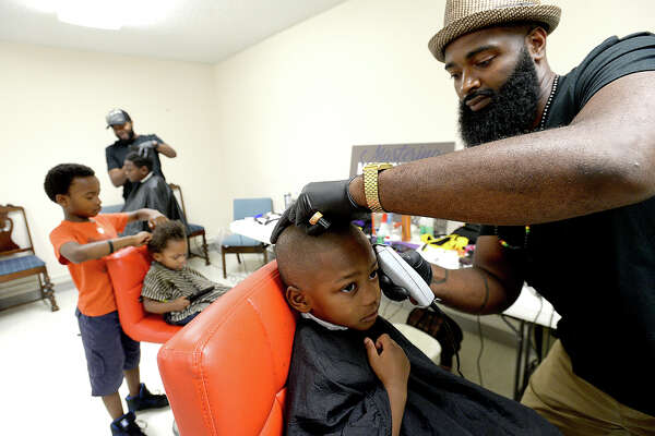 """Three-year-old Greysen Kelly patiently sits as he gets a fade cut from Ashford Garner during the second annual """"A Day at Linda's Lighthouse"""" back to school event held at Kingdom Dominion Church in Port Arthur Saturday. Families gathered in rooms throughout the church, taking in wellness checks, free haircuts and styles, crafts, entertainment, raffle drawings, and the big supply-filled backpack give away. The event is held in honor of Linda Griffin Lucas, who was active in serving the Port Arthur community and those in need for many years before passing in 2011. Event organizers say this year's numbers have doubled since last year's kickoff, with over 500 residents attending. Photo taken Saturday, August 19, 2017 Kim Brent/The Enterprise"""