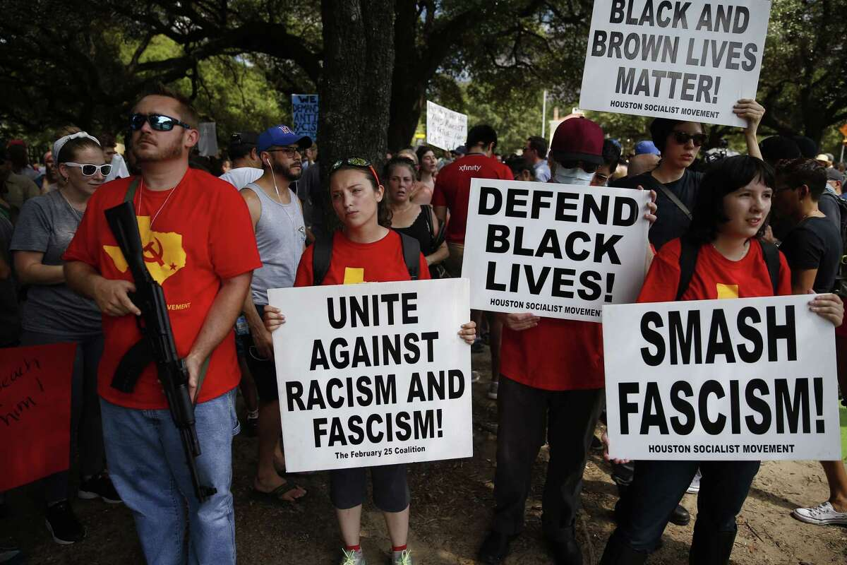"""Above: Protesters demonstrate outside Sam Houston Park during a rally against a Confederate monument and racism on Saturday. Right: Rusty Johnson carries flags as he joins the counterprotest against the removal of the statue called """"The Spirit of the Confederacy."""""""