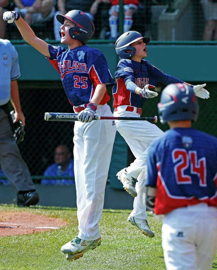 Jackson, N.J.,'s Anthony Abbonizio, left, and John Grano, right rear, celebrate scoring on a double by Chris Chatnick off Grosse Pointe, Mich., pitcher Joey Randazzo in the second inning of an elimination baseball game in United States pool play at the Little League World Series tournament in South Williamsport, Pa., Saturday, Aug. 19, 2017. (AP Photo/Gene J. Puskar) ORG XMIT: PAGP112 Photo: Gene J. Puskar / Copyright 2017 The Associated Press. All rights reserved.