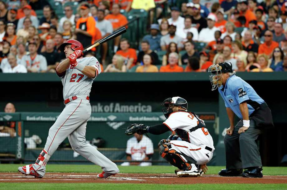 Los Angeles Angels' Mike Trout, left, hits a solo home run in front of Baltimore Orioles catcher Welington Castillo, center, and home plate umpire Tom Hallion in the first inning of a baseball game in Baltimore, Saturday, Aug. 19, 2017. (AP Photo/Patrick Semansky) ORG XMIT: MDPS103 Photo: Patrick Semansky / Copyright 2017 The Associated Press. All rights reserved.