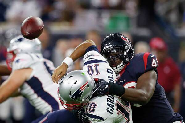 Texans outside linebacker Tony Washington, right, sacks quarterback Jimmy Garoppolo and in doing so forces a fumble in the third quarter Saturday night at NRG Stadium.