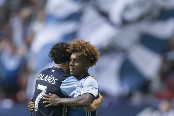 Vancouver Whitecaps' Christian Bolanos, left, and Yordy Reyna celebrate Reyna's goal against the Houston Dynamo during the first half of an MLS soccer match in Vancouver, British Columbia, Saturday Aug. 19, 2017. (Darryl Dyck/The Canadian Press via AP)