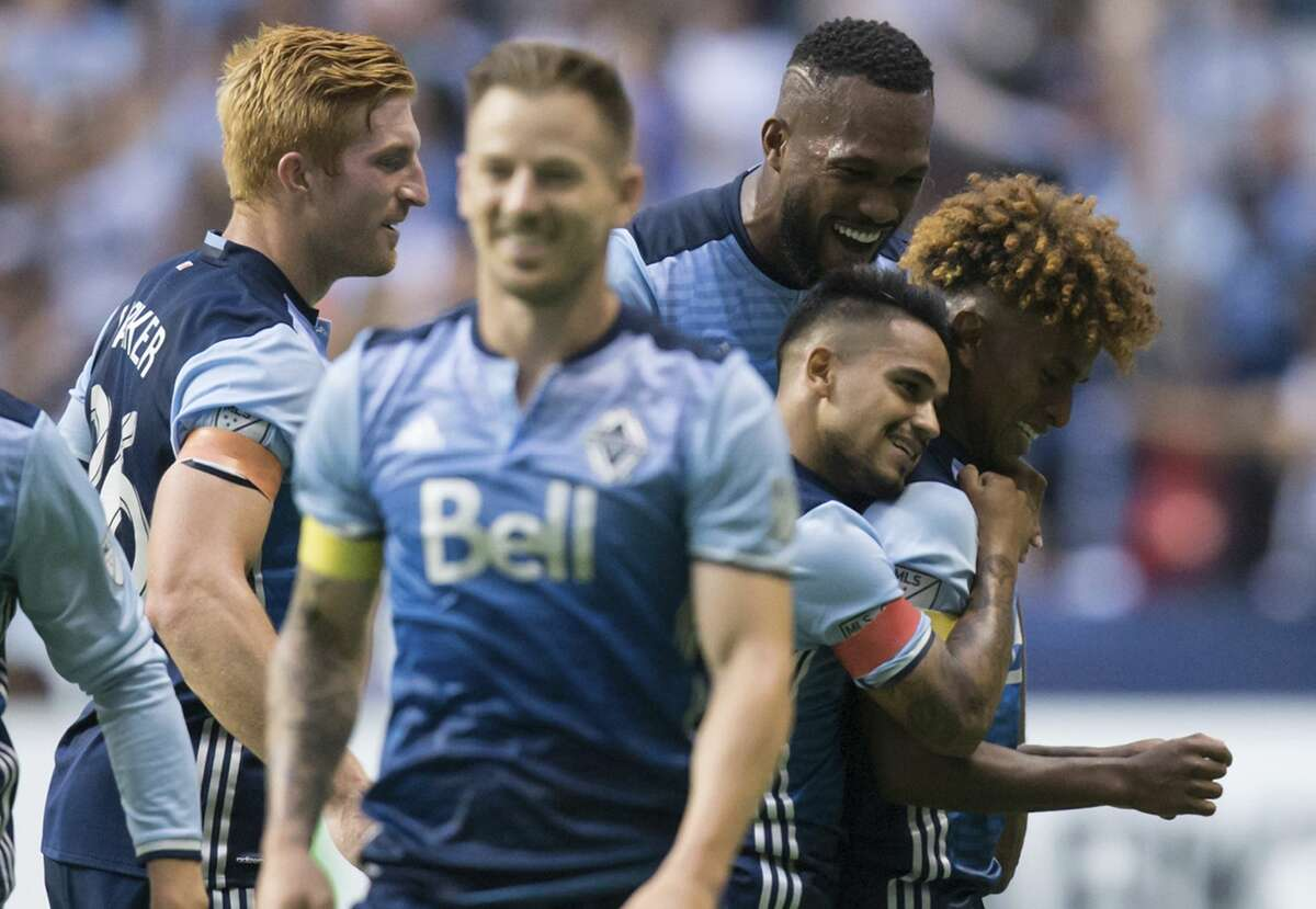 Vancouver Whitecaps' Tim Parker, Kendall Waston, Cristian Techera and Yordy Reyna, from left in back, celebrate Reyna's goal against the Houston Dynamo during the first half of an MLS soccer match in Vancouver, British Columbia, Saturday Aug. 19, 2017. (Darryl Dyck/The Canadian Press via AP)