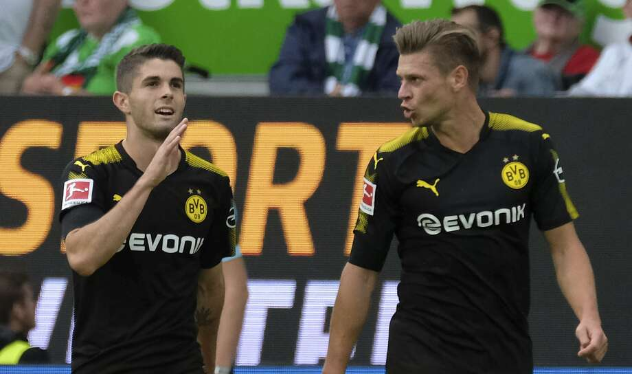Dortmund's Christian Pulisic (left), who plays for the U.S. national team, celebrates scoring the first goal against Wolfsburg. Photo: Peter Steffen, Associated Press