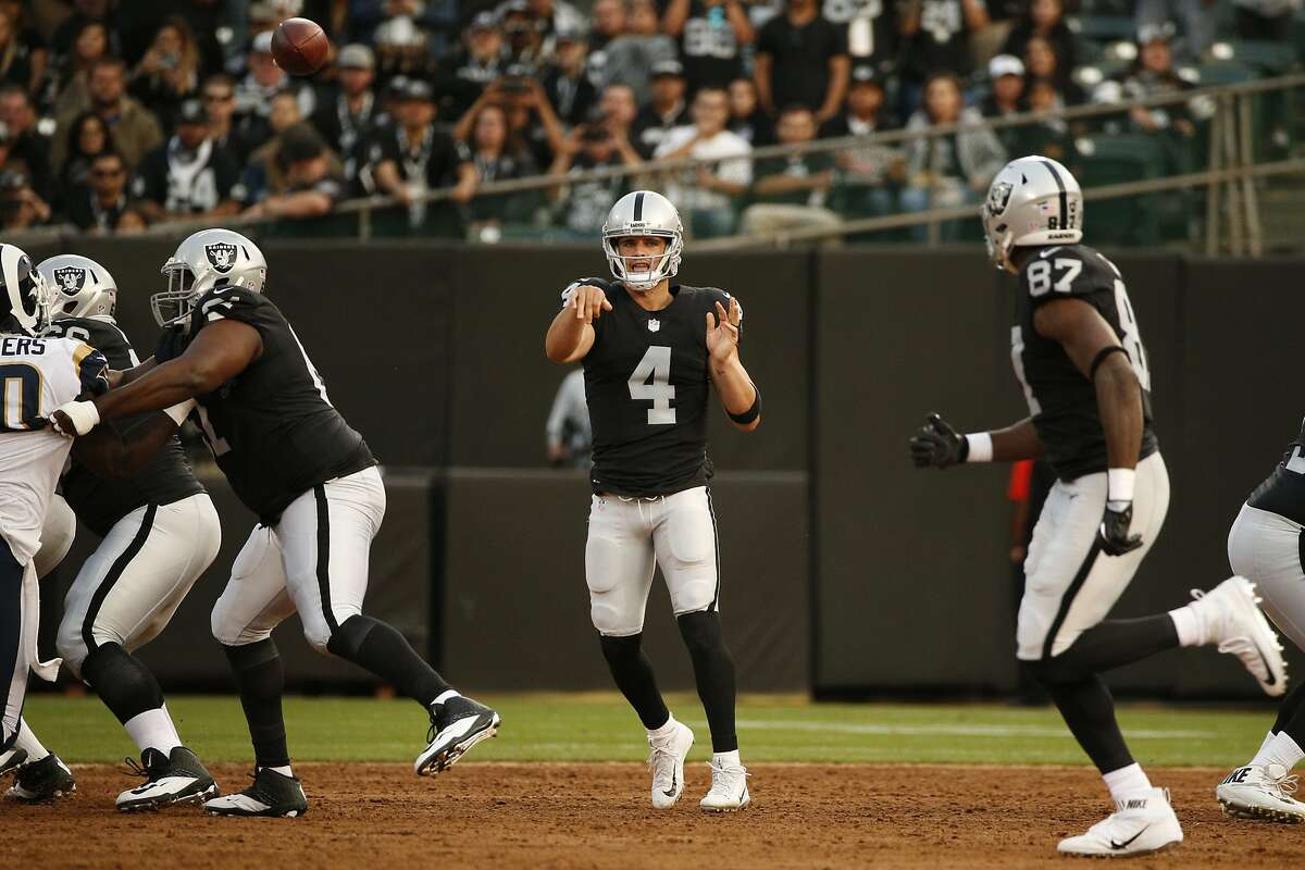 Oakland Raiders quarterback Derek Carr (4) makes the pass to tight end Jared Cook (87) during the first half of an NFL preseason football game between the Oakland Raiders and the Los Angeles Rams on Saturday, Aug. 19, 2017, at the Oakland Coliseum in Oakland, Calif. The Rams lead 17-14 at halftime.