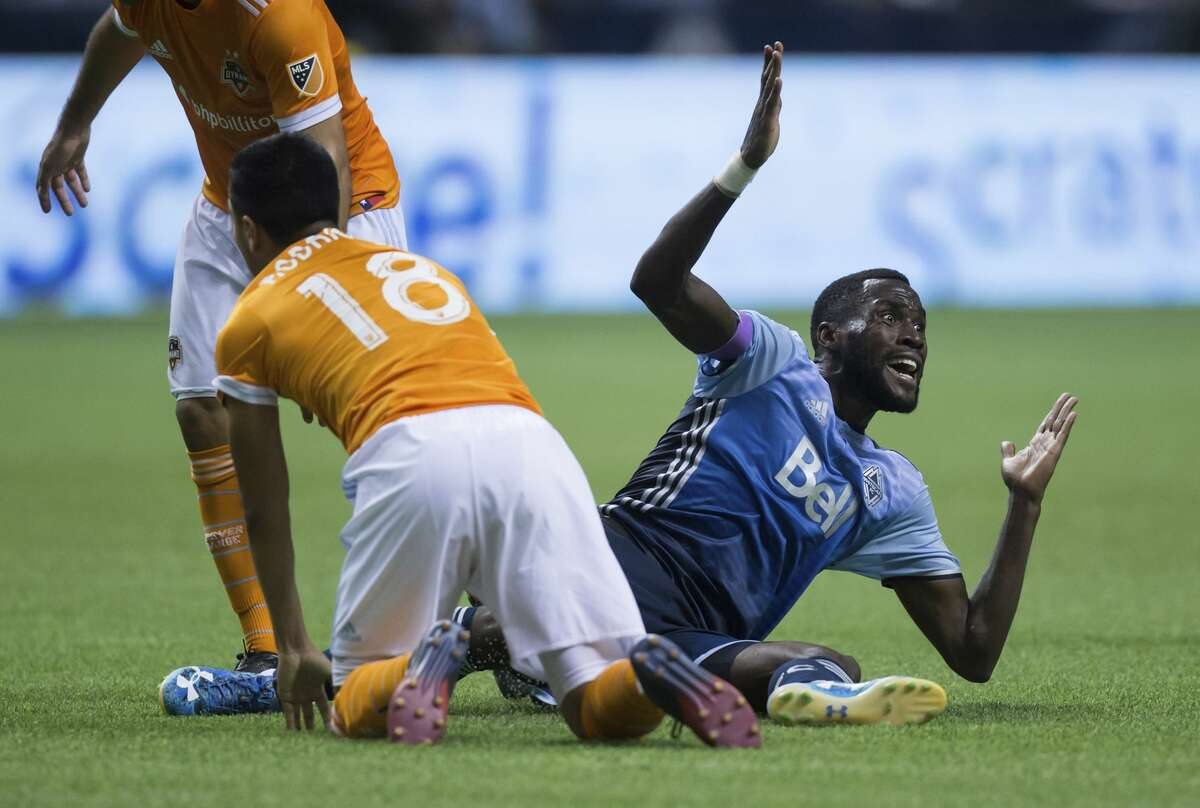 Vancouver Whitecaps' Tony Tchani, right, reacts to the referee after knocking Houston Dynamo's Memo Rodriguez to the ground during the second half of an MLS soccer match in Vancouver, British Columbia, Saturday Aug. 19, 2017. (Darryl Dyck/The Canadian Press via AP)