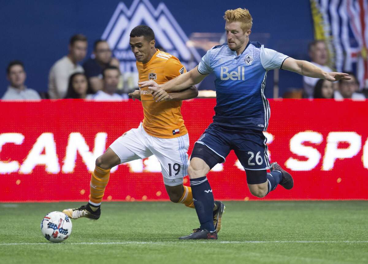 Houston Dynamo's Mauro Manotas, left, moves the ball past Vancouver Whitecaps' Tim Parker during the second half of an MLS soccer match in Vancouver, British Columbia, Saturday Aug. 19, 2017. (Darryl Dyck/The Canadian Press via AP)