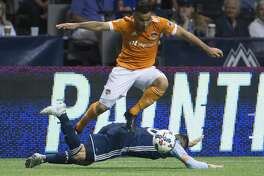 Houston Dynamo's Alex leaps over Vancouver Whitecaps' Jake Nerwinski after taking the ball from him during the second half of an MLS soccer match in Vancouver, British Columbia, Saturday Aug. 19, 2017. (Darryl Dyck/The Canadian Press via AP)