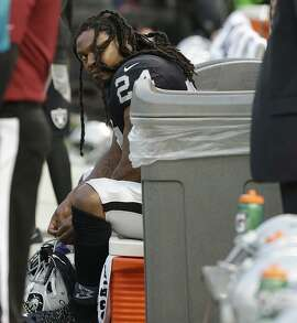 """Running back Marshawn Lynch, an Oakland native, sits for """"The Star-Spangled Banner"""" before the Raiders' exhibition game against the Los Angeles Rams at the Coliseum."""