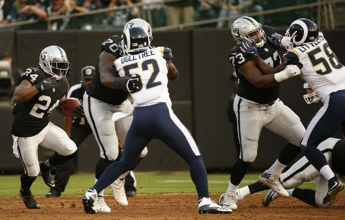 Raiders running back Marshawn Lynch (left) got his first action of the preseason, playing one series against the Rams.