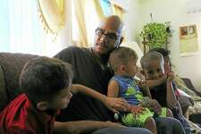 Wigberto 'George' Ortiz sits on a couch with his sons, from left: Lorenzo, 6; Matteo, 16 months; Marcelo, 4; and Vitally, 7, in New Britain. Ortiz completed a program aimed at helping fathers who have been charged in domestic violence incidents.
