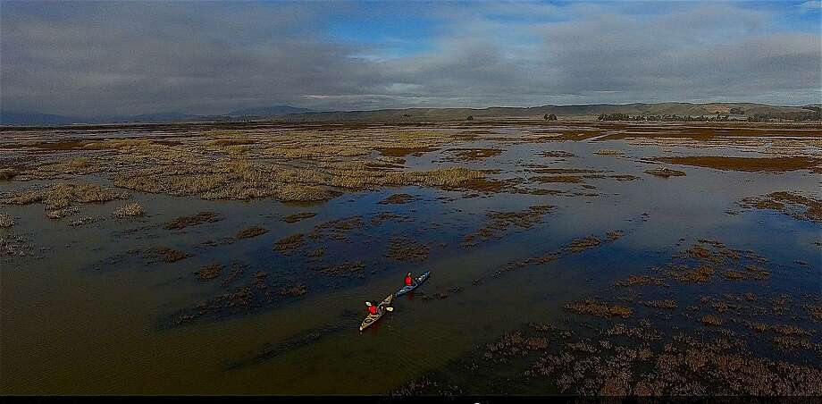 In a video image captured from a drone, biologist Robert Eddings and Tom Stienstra paddle kayaks in the Suisun Marsh. Photo: Tom Stienstra, Courtesy Barbary Coast Productions