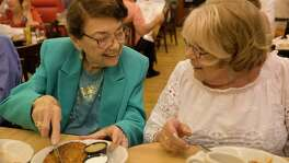 Holocaust survivors Rosine Chappell, left, and Ruth Steinfeld have conversations while sharing a potato Latke during lunch at Kenny & Ziggy's New York Delicatessen with three other Holocaust survivors Thursday, Aug. 10, 2017, in Houston.