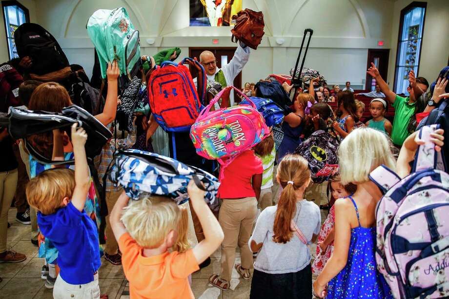 Kids hold their backpacks in the air at St. Francis Episcopal Church as the Rev. Robert Wismer blesses the backpacks during the morning service ahead of the start of the school year Sunday, Aug. 20, 2017 in Houston. ( Michael Ciaglo / Houston Chronicle ) Photo: Michael Ciaglo, Staff / Michael Ciaglo