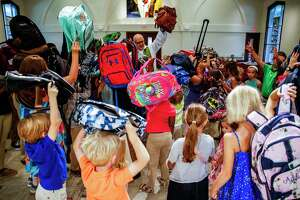 Kids hold their backpacks in the air at St. Francis Episcopal Church as the Rev. Robert Wismer blesses the backpacks during the morning service ahead of the start of the school year Sunday, Aug. 20, 2017 in Houston. ( Michael Ciaglo / Houston Chronicle )