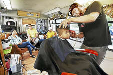 Catherine Avalone / Hearst Connecticut Media Luis Gonzalez, owner of the Mobile Barber Shop at the corner of Lloyd and Chapel Streets, gives a haircut to 5-year-old East Haven resident Matias Perkins as his father, Calvin Perkins, waits with his wife, Vanessa, in the waiting area with Ramon Martinez.