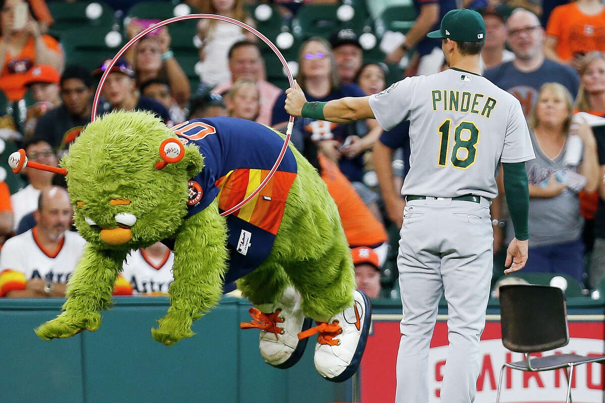 Houston Astros mascot Orbit jumps through a hoop held up by Oakland Athletics shortstop Chad Pinder (18) before the Houston Astros take on the Oakland Athletics at Minute Maid Park Sunday, Aug. 20, 2017 in Houston.