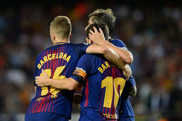 Barcelona's Argentinian forward Lionel Messi (R) celebrates with teammates after scoring during the Spanish league footbal match FC Barcelona vs Real Betis at the Camp Nou stadium in Barcelona on August 20, 2017. / AFP PHOTO / Josep LAGOJOSEP LAGO/AFP/Getty Images