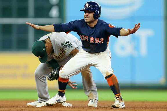 Houston Astros second baseman Jose Altuve (27) motions that he is safe after successfully stealing second base past Oakland Athletics shortstop Marcus Semien (10) as the Houston Astros take on the Oakland Athletics in the eighth inning at Minute Maid Park Sunday, Aug. 20, 2017 in Houston.