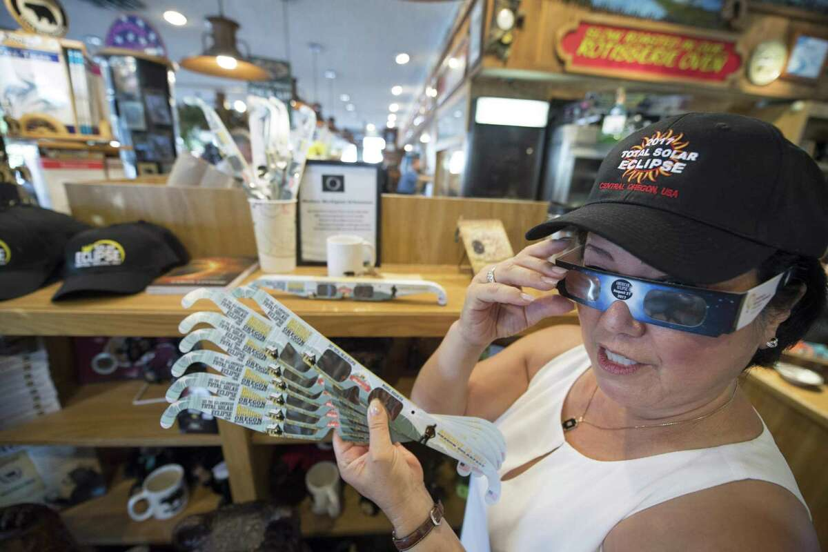 Carol Jensen at the Black Bear Diner displays a hat and eclipse glasses Saturday in Madras, Oregon. The diner is selling merchandise for Monday's total solar eclipse that will be visible across the continental U.S.