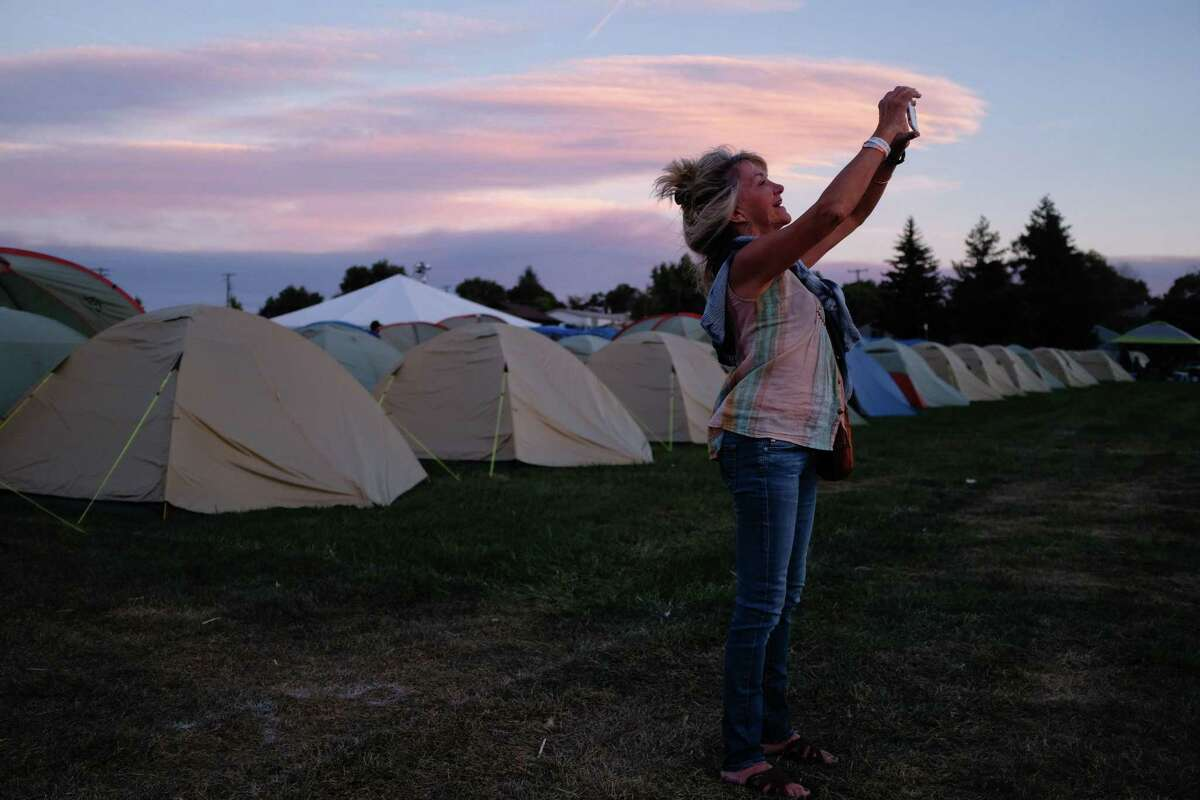 Suzanne Rapley of Santa Barbara, California, takes a photo at sunset with her iPhone on Friday. She is one of many total solar eclipse enthusiasts gathering in Madras, Oregon, for Monday's eclipse.