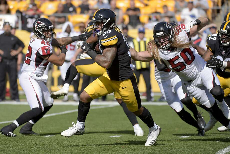 Steelers running back James Conner dashes between Falcons defensive end Brooks Reed (50) and outside linebacker Duke Riley. Photo: Fred Vuich, Associated Press