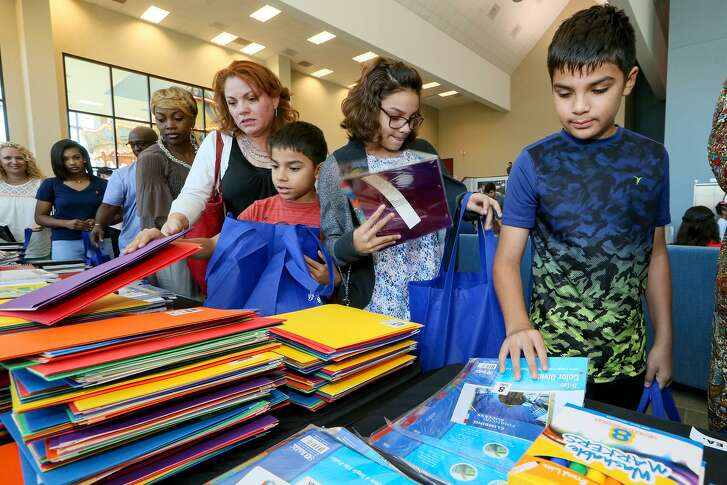 Marcos Perez (from right), 9, Isabella Perez, 12, Alejandro Perez, 7, Valerie Perez and other members of Summit Christian Center help in stuffing bags of school supplies after the Sunday service on Sunday, Aug. 20, 2017.   The congregation put together 660 bags of school supplies and 1,200 weekend snack bags for donation to Olmos Elementary School, which the church has adopted, after raising $20,000 for the effort.  MARVIN PFEIFFER/ mpfeiffer@express-news.net