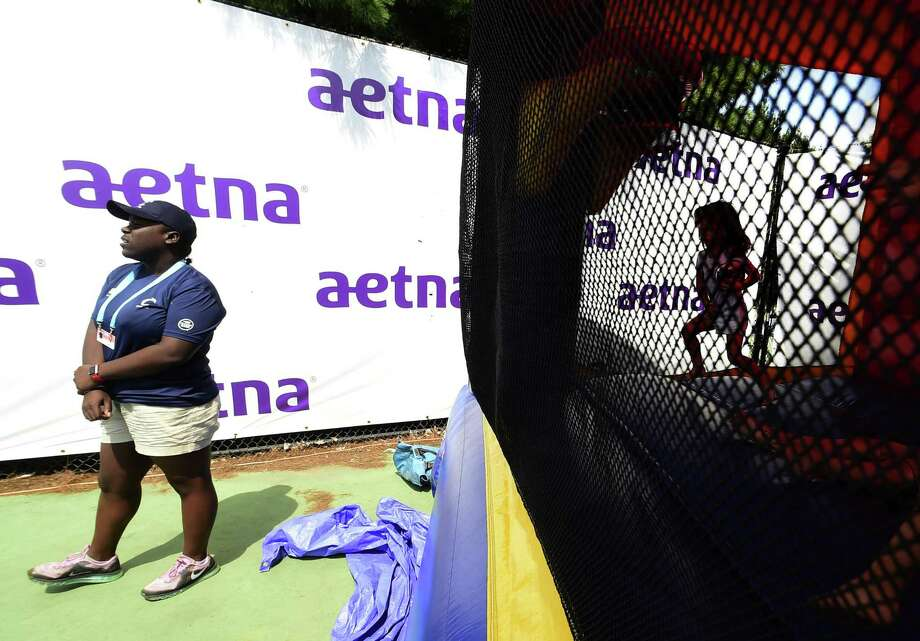 (Peter Hvizdak / Hearst Connecticut Media) New Haven,Connecticut: Sunday, August 20, 2017.  Volunteer Milan Yorke, 16, of Ansonia, a Connecticut Open tennis tournament volunteer as she watches over the Aetna Fit Zone  inflatable moon walk bounce house's Sunday afternoon in an upper court area at the Connecticut Tennis Center in New Haven. Photo: Peter Hvizdak / Hearst Connecticut Media / New Haven Register