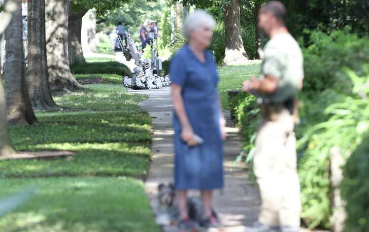 """A neighbor and her dog who got little to close to the crime scene was asked to move back as a robot was used in the background. Houston Police, ATF and the FBI respond to a """"special assignment"""" in the 2000 block of Albans Sunday, Aug. 20, 2017, in Houston."""