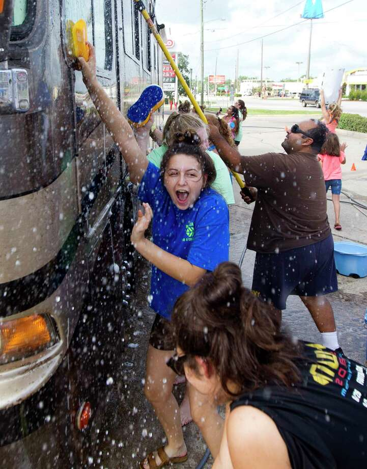 Kylee Skates screams as she is sprayed with water during a car wash to raise money for the Magnolia West High School band's trip to the Citrus Bowl in January 2018, Saturday, Aug. 19, 2017, in Conroe. Photo: Jason Fochtman, Staff Photographer / © 2017 Houston Chronicle