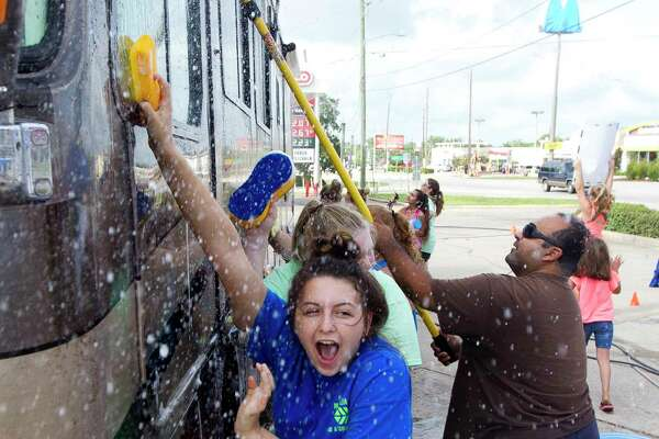Kylee Skates screams as she is sprayed with water during a car wash to raise money for the Magnolia West High School band's trip to the Citrus Bowl in January 2018, Saturday, Aug. 19, 2017, in Conroe.