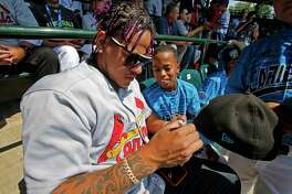 Santiago, Dominican Republic's Ronald Rosario, center, gets his cap signed by St. Louis Cardinals' Carlos Martinez in the stands at Lamade Field during a baseball game between Fairfield, Conn., and Lufkin, Texas in United States pool play at the Little League World Series tournament in South Williamsport, Pa., Sunday, Aug. 20, 2017. The Pirates will be playing the St. Louis Cardinals in Bowman Stadium in Williamsport, Pa., on Sunday Night Baseball. (AP Photo/Gene J. Puskar) ORG XMIT: PAGP112