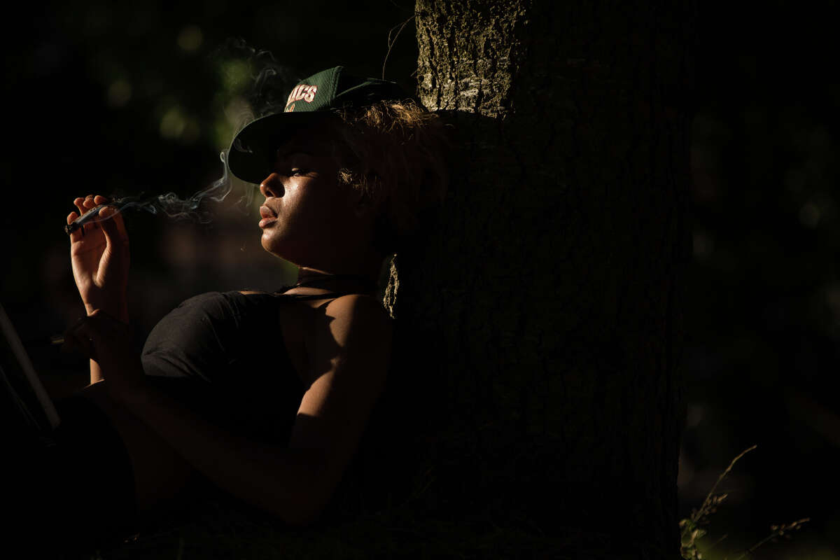 A woman smokes while lounging against a tree during Hempfest at Myrtle Edwards Park on Sunday, Aug. 20, 2017.