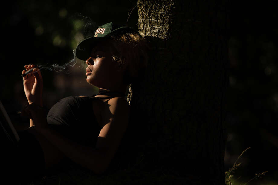 A woman smokes while lounging against a tree during Hempfest at Myrtle Edwards Park on Sunday, Aug. 20, 2017. Photo: GRANT HINDSLEY, SEATTLEPI.COM / SEATTLEPI.COM