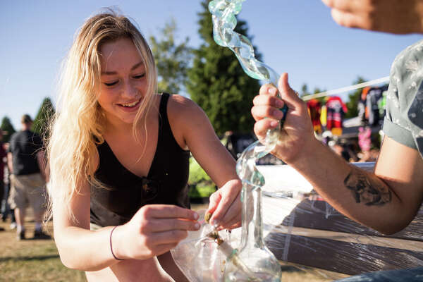 Jade Cottrell packs a slide in a bong during Hempfest at Myrtle Edwards Park on Sunday, Aug. 20, 2017.