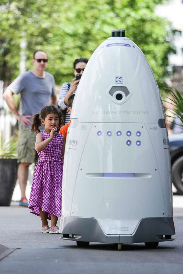Viola Shaw, 4, left, waves at a new security robot, ROD2 - a play on River Oaks District and the famous Star Wars droid - as it patrols in River Oaks District on Aug. 18, 2017, in Houston. Photo: Michael Ciaglo, Staff / Michael Ciaglo