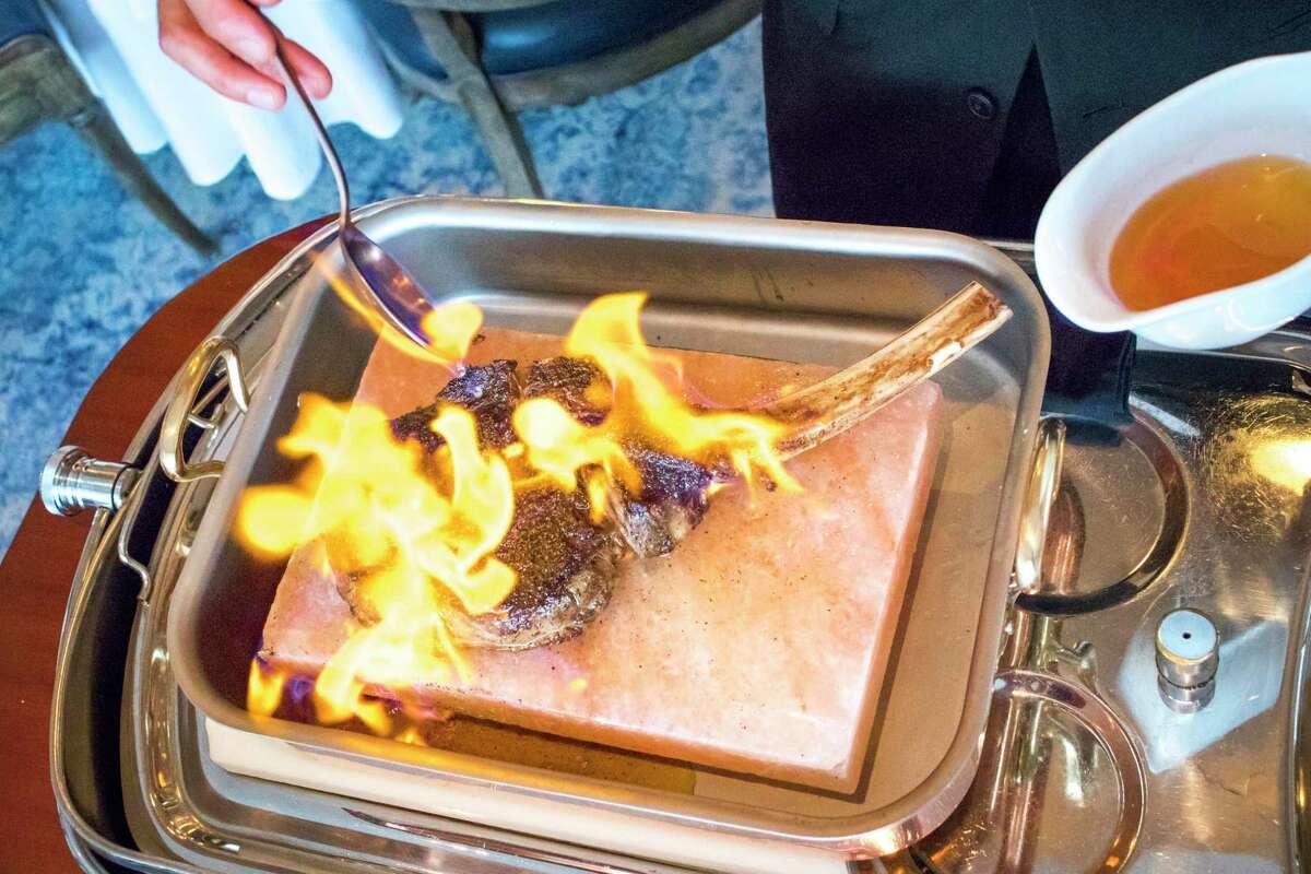Texas Long Bone Akaushi Ribeye in cognac flambe on the Chateau menu at La Table restaurant, Houston.