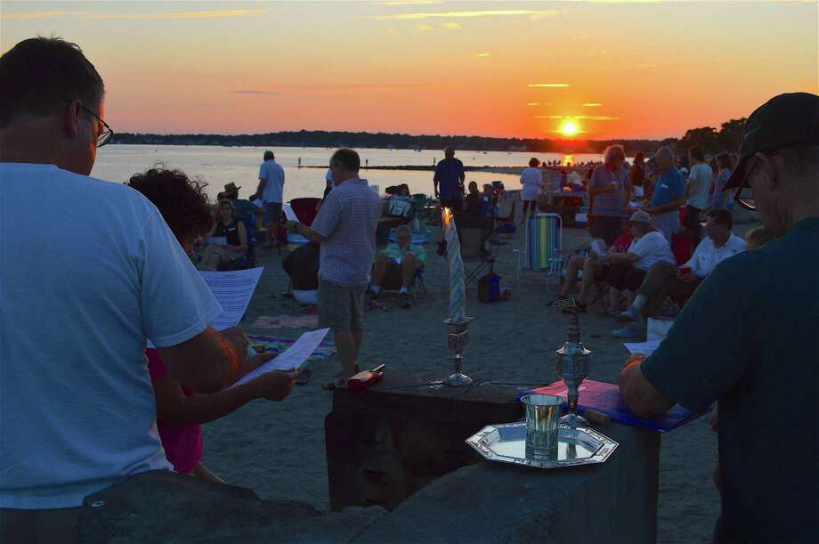 Sundown marks the beginning of the annual Havdalah service of the Congregation for Humanistic Judaism of Fairfield County at Compo Beach on Saturday in Westport. Photo: Jarret Liotta / For Hearst Connecticut Media / Westport News Freelance