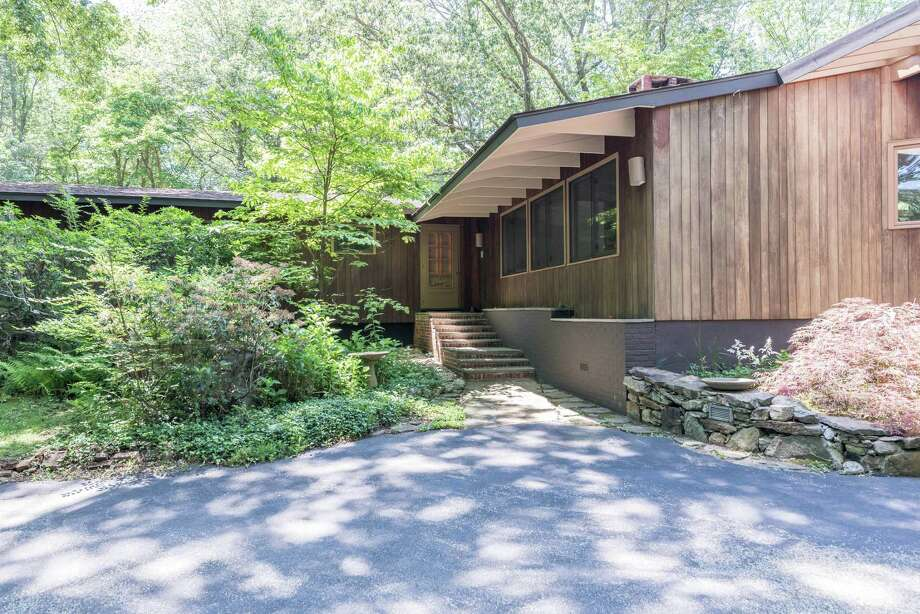 The mid-century modern house at 68 Indian Waters Drive sits on a 3.14-acre level and sloping wooded property; the trees providing a secluded setting. Photo: Contributed Photos
