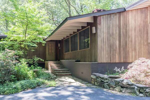 The mid-century modern house at 68 Indian Waters Drive sits on a 3.14-acre level and sloping wooded property; the trees providing a secluded setting.