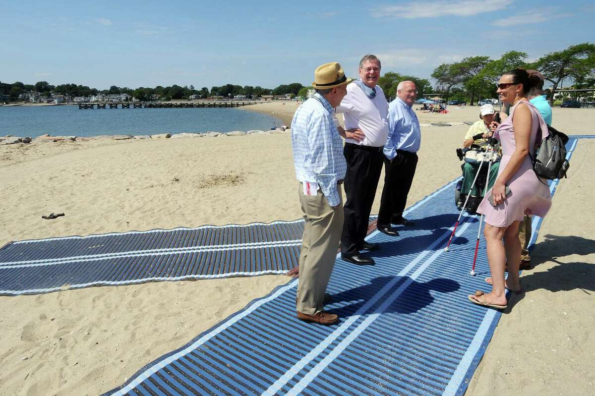 Stamford mayor David Martin (center right), joined by members of the Access 4 All (A4A) Committee, examines the expanded Mobi Mat at Cummings Beach on Thursday, August 17, 2017. The Mobi Mat allows for beach access to people in wheelchairs, with strollers, and the blind.