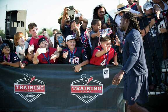 Houston Texans defensive end Jadeveon Clowney, right, slaps hands with fans as he walks to practice during training camp at The Methodist Training Center on Monday, Aug. 21, 2017, in Houston.