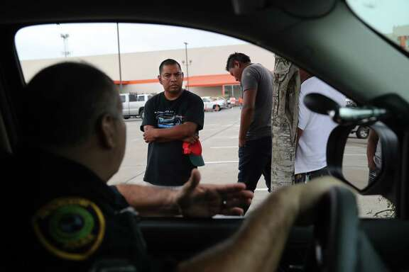 "Houston Police Department officer Al Yanez, 51, tries to reassure Felix Rodriguez, 30, that he wouldn't be asking about his status after SB4 takes effect, Rodriguez remained uncertain. Yanez drives around the parking lot of Home Depot talking to the daily workers about Texas law, known as Senate Bill 4, which bans ""sanctuary cities,"" Tuesday, Aug. 8, 2017, in Houston."