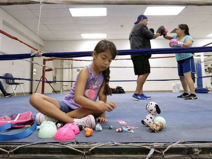 Shae Delgado plays with her toys as her father Herman Delgado, left, trains one of his fighters in the ring at the Armijo Recreation Center.