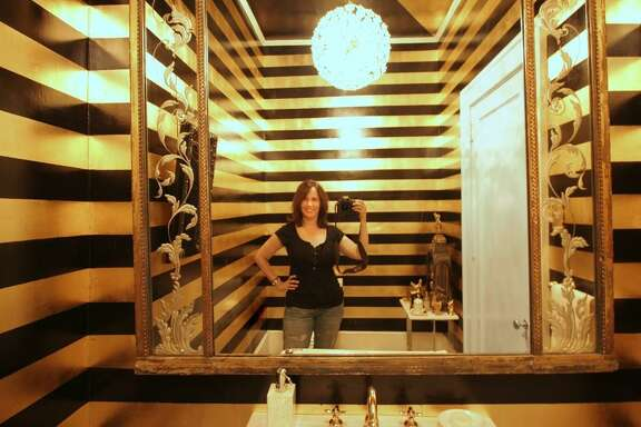 Painter Lisa Moon takes a selfie in a bold powder room in a Monte Vista home.