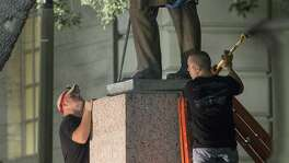 A statue of Confederate Postmaster General John Reagan is removed from the Main Mall of the University of Texas at Austin. Three other Confederate statues also were taken down.