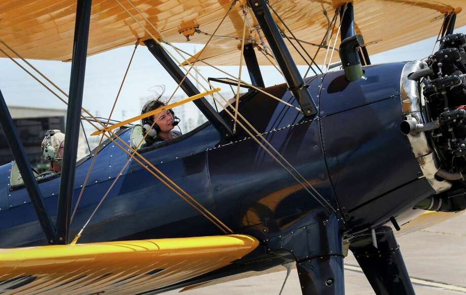Houston Chronicle reporter Maggie Gordon, right, rides in a PT-17 as it prepares to take off from Galveston Island to relocate to the Lone Star Flight Museum's new home. Photo: Jon Shapley, Houston Chronicle / © 2017 Houston Chronicle